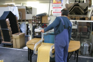 <p>スタッフの方がそれぞれの持場で作業に取り組んでいます。<br /> これは座面と脚を取り付ける機械です。プレスにて一気に挟み込みます。</p>