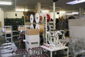 <p>実際の作業場へ。<br /> たくさんのビニールコードやパイプ。これから組み立てられていく椅子のパーツがずらり。</p>